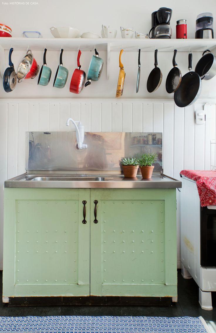 Cozinha com bancada de inox, armário na cor verde água e prateleira com ganchos para pendurar as panelas.