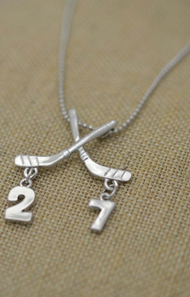 This beautiful piece of custom hockey jewelry features two silver plated numbers that hang from the crossed hockey sticks! It will sure become your hockey star's favorite hockey gift! Makes a great hockey birthday gift too!