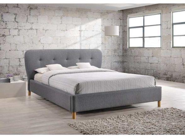 Łóżko BELLA 160x200 to fantastyczne łóżko do sypialni. Łóżko tapicerowane jest szarą tkaniną i opiera się na drewnianych nóżkach.