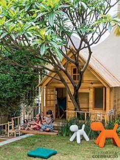 Uma casa de bonecas feita de madeira no meio do jardim - Casa