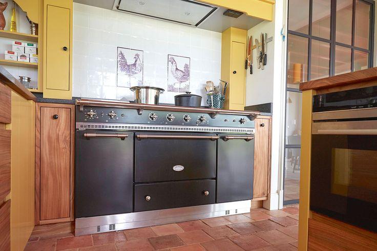 Lacanche fornuis in een landelijke keuken met gele accenten. Het fornuis is voorzien van o.a. een steamer en nog veel meer.
