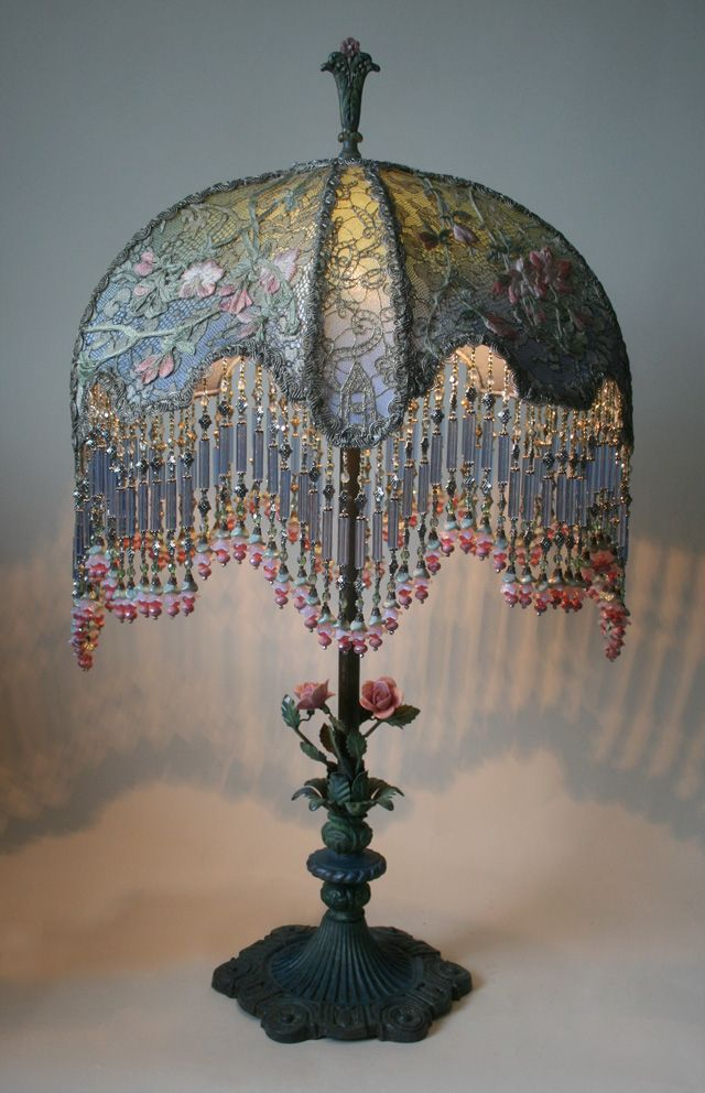 Ornate 1920s metal table lamp with dimensional porcelain roses holds a Cherry Blossom Moon shade in soft green and blue and then strewn with pale pink cherry blossom appliqués. The porcelain flowers show a little age but are in good vintage condition. Antique silver metallic lace overlay the panels. Hand beaded, fringe with flower drop ends adorn the shade.