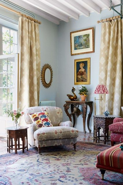 Blue Living Room with Comfortable Armchair in Living Room Design Ideas. Pale blue living room with large armchair, framed hanging prints, antique rug and furniture.