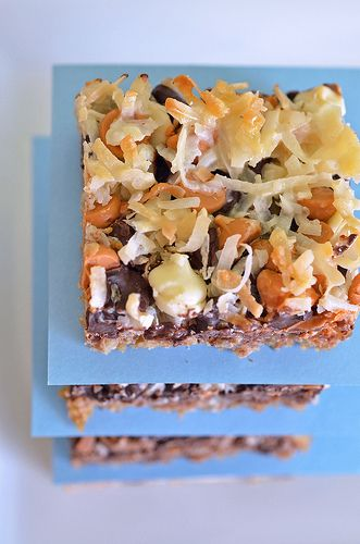 Seven-Layer Bars (or Magic Bars)    Yield: 18 bars    1 cup sweetened flaked coconut  8 tablespoons unsalted butter  9 graham crackers, crushed  1 cup finely chopped walnuts  1 cup semisweet chocolate chips  1/2 cup white chocolate chips  1/2 cup butterscotch chips  1 (14 oz) can sweetened condensed milk