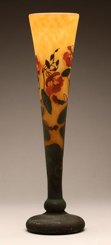 Lot# 1155 A large Daum Nancy cameo art glass 'Nasturtium' vase.Early 20th century, marked ''Daum / Nancy'' with Croix de Lorraine, of trumpet-form, with acid-cut back decoration of red-orange nasturtium flowers with blue-green stems on a yellow-orange ground, 22.75'' H x 6.25'''' Dia., est: $1500/2500 *Price Realized: $3,313.75