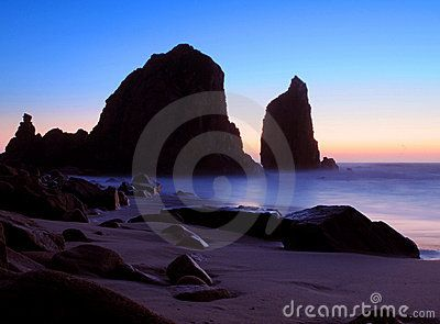 A colorful sunset on Praia da Ursa beach at Cabo da Roca, Portugal, with large rocks and boulders silhouetted against the sky.
