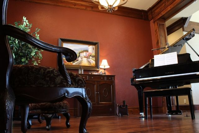 This Beautiful Red Colored Piano Room With Wood Flooring