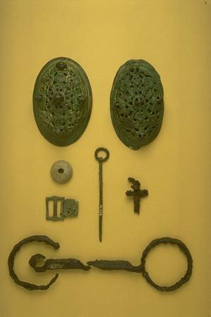 These grave goods were found along with some human bones eroding from the sand dunes at Reay in Caithness in 1912. They are characteristic Scandinavian grave goods, indicating a woman's burial dating to around 900 to 1000. Other Viking graves were found nearby.  The grave goods comprise brass oval brooches, a bronze ring-headed pin, a steatite spindle whorl, a tinned bronze buckle, an iron horse bit and a small pair of corroded iron tweezers. http://nms.scran.ac.uk/