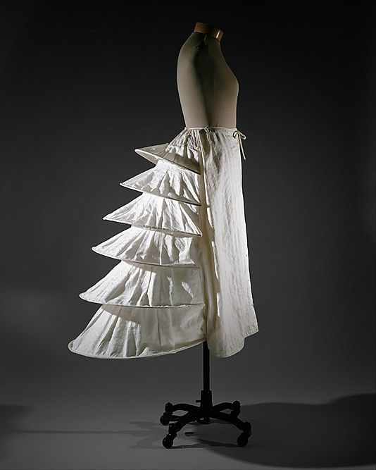 Bustle(undergarment structure)- Constructed of either small down or cotton filled pads. Tied around the waist at th back and helped to hold out ladies skirts.