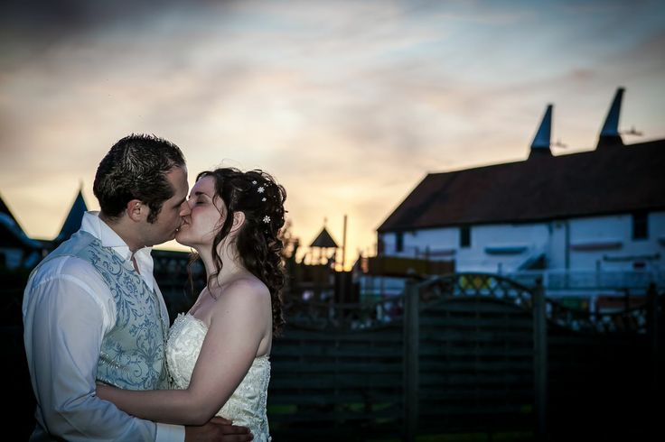 A late evening shot of a bride and groom with lush evening skies and oast houses in the background (re-worked 2014)