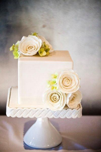 A single box-tier carrot cake with pearlised ivory fondant and green and white ranunculus flowers. Photos by GM Photgraphics