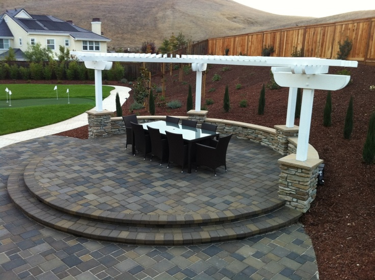 Raised seating area on an elevated patio radius with a stackstone seat wall and curved arbor.