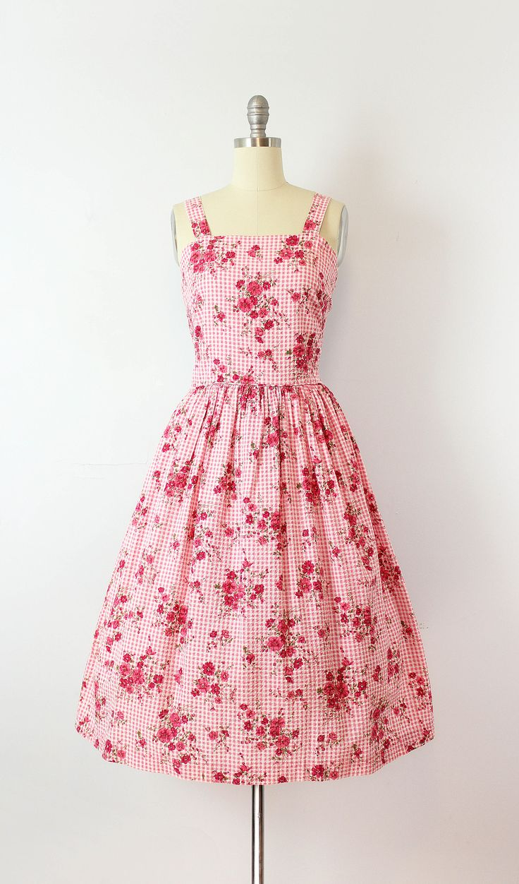 Vintage 1950s cotton seersucker sundress in a pink and white gingham print with clusters of red and pink flowers and green leafy stems. Wide shoulder straps with a darted and fitted bust. Fitted waist with piping trim and a top gathered skirt with a full fit through the hips. Dress is made of a soft and lightweight cotton with the typical lightly puckered texture of seersucker. Fluid and moves easily (not crisp). Bodice is lined in white cotton and the skirt is unlined. Metal zipper up the…