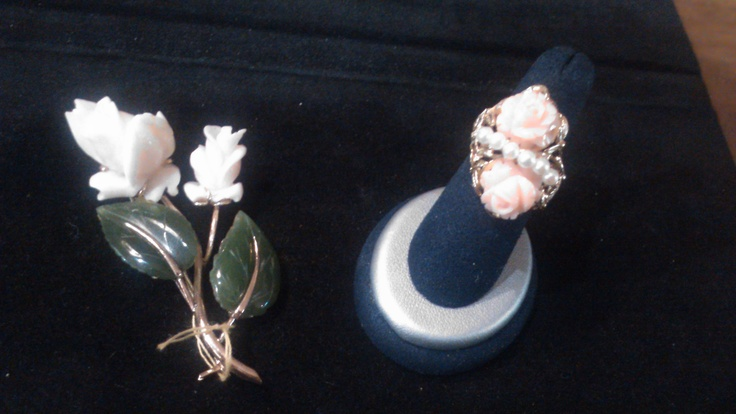 Leaves of fine jade accompany flowers shaped of coral upon the left as pearls run between roses in coral upon the right, yellow gold adorning both the pin and the ring.