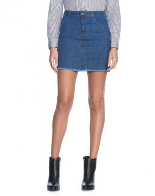 Saia jeans curta cintura alta com padrão de lavagem na cor média, cintura alta e recortes laterais. acabamento em barra fio oferece leve desfiado ao modelo.