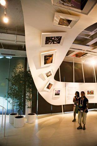"""Säulen - """"Geschichte erzählen""""  Art attached to an upside down curving serpentine wall."""