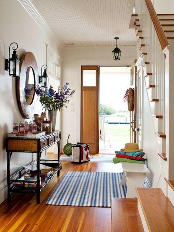 une console en bois, miroir rond à l'encadrement en bois, escalier élégant, jolies appliques murales