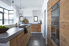 Cucina piccola stile moderno e rustico con mobili in legno massello e piano lavoro e pavimento in cemento