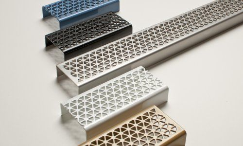 Marc Newson grates available from Stormtech. The decorative grates are in the designer's signature tessellated hexagonal pattern, made from 12 guage stainless steel and are available in five finishes.  Dimensions: 65mm wide and come in 4 lengths 900, 1000, 1200, 1500 with kits up to 6000mm. http://www.stormtech.com.au/products/mnd-series-series/65mndi25