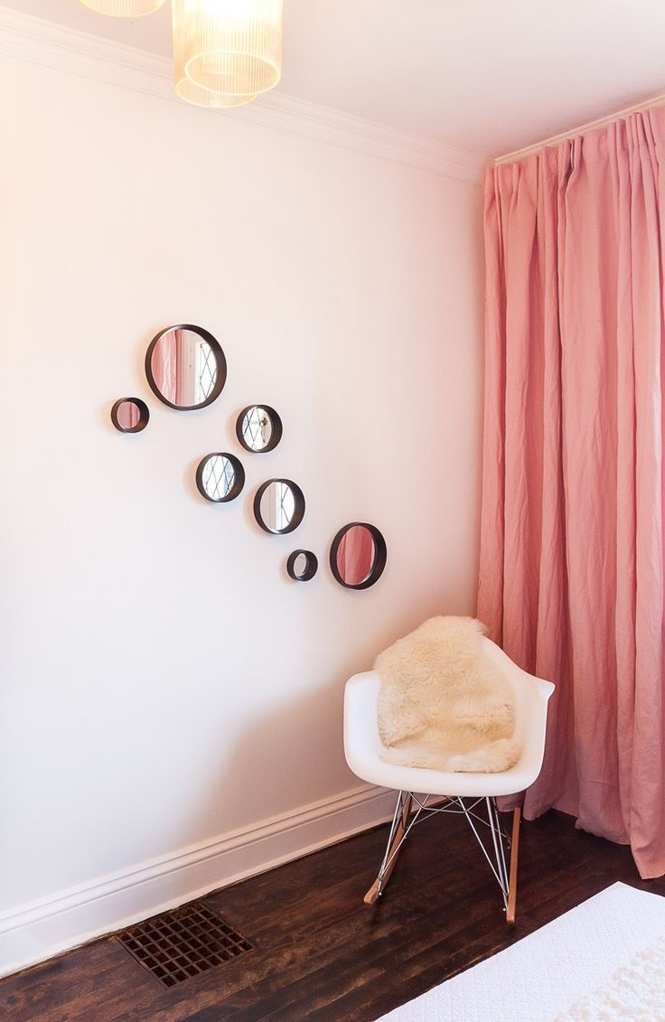 Small round mirrors have been used to create art on this bedroom wall.