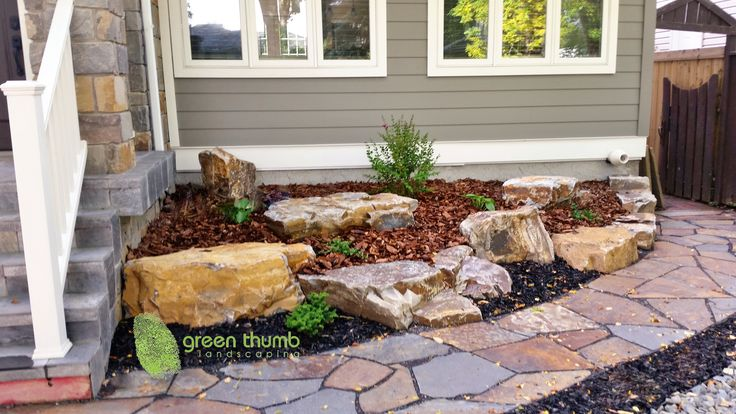This is a natural stone flower bed accented with a flagstone path and mulches. We used boulders to create elevation and plants and mulch to soften the look. A rock garden is a beautiful way to accent your home.