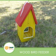 Madeira pendurado alimentador do pássaro com o telhado vermelho e amarelo corpo