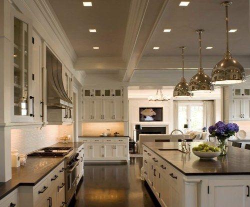 Amazing floor plan for dream kitchen - Creamy white kitchen cabinets & kitchen island with black granite countertops, sink in kitchen island and industrial pendants.