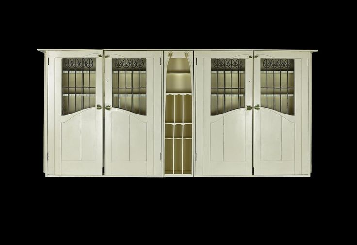 White painted oak bookcase with leaded glass doors in three sections, and with a single top shelf, designed by Charles Rennie Mackintosh for the Library at Dunglass Castle, Bowling, Dunbartonshire, 1900