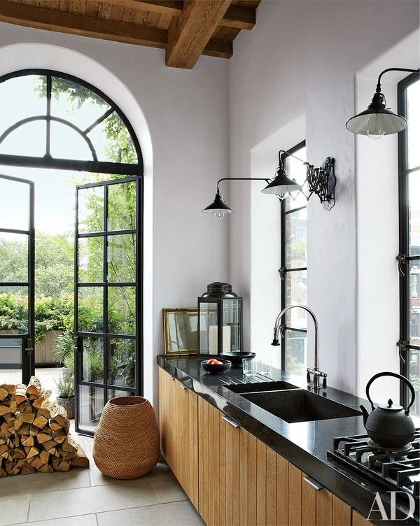 In this Manhattan house decorated by Alfredo Paredes, industrial light fixtures and bluestone countertops complement white-oak cabinetry in the kitchen; the pulls are by E. R. Butler | archdigest.com
