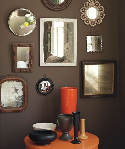 DECORATING TIP: Ornamental mirrors, especially dramatic on a dark wall, make a striking wall display.