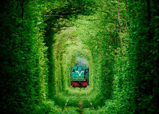 Tunnel Of Love | Ukraine. Located near the town of Kleven, this luscious green tunnel provides passage for a private train that provides wood to a local factory. Measuring 1.8 miles long, the picturesque rail route in Eastern Europe is also a popular spot for lovers.