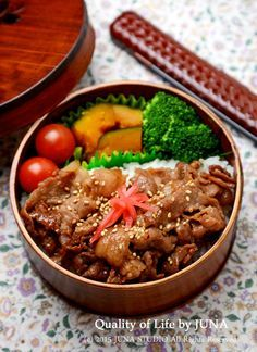 Japanese Bento Box featuring grilled sesame pork atop a bed of rice, pickled ginger, stewed kabocha squash, and broccoli & tomatoes