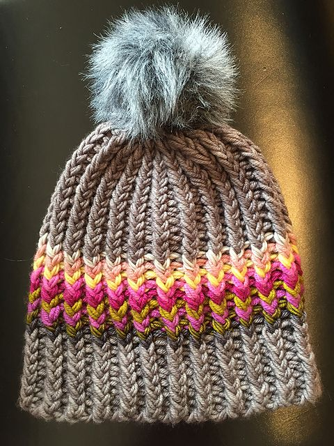 Free knitting pattern for Twisted Ribster Hat pattern by Betsy Ioannou. This fun, easy, quick ribbed hat busts the stash. It uses a variety of yarns held in multiple strands to get a super chunky gauge. pompom