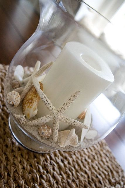 Starfish, shells & sand in hurricane glass with candle for a Summer centerpiece.
