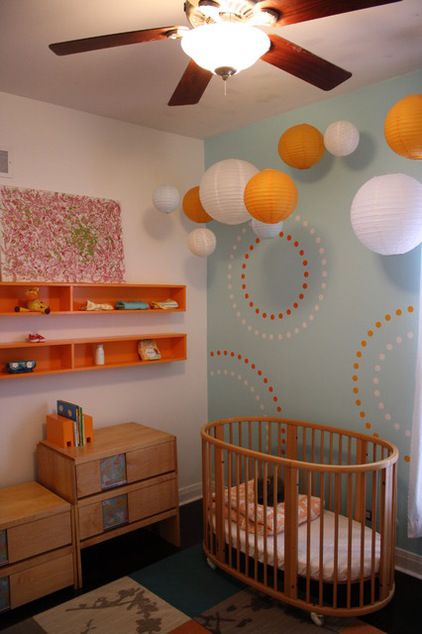 A baby's room is the perfect place to play with miniature paper ball lanterns in a few sizes. Orange and white were play off the wallpaper as though the little dots on the wall have somehow come to life.