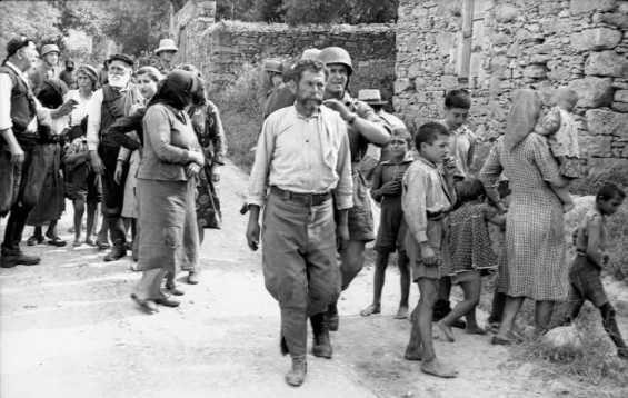 ΠΗΓΕ ΝΑ ΞΕΦΥΓΕΙ, ΟΜΩΣ ΤΟΝ ΑΝΑΚΑΛΥΨΑΝ ΤΕΛΕΥΤΑΙΑ ΣΤΙΓΜΗ και τον οδηγούν στον ελαιώνα, στην άκρη του χωριού όπου είχαν συγκεντρώσει και τους άλλους. Εκεί βρίσκεται και το εκτελεστικό απόσπασμα του υπολοχαγού Τρέμπες. Οι γέροι, οι γυναίκες και τα παιδιά μετά τη διαλογή περιμένουν από λεπτό σε λεπτό τη συμφορά των δικών τους.