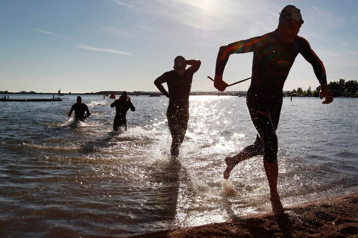 Ironman competitors run from the waters of the Boulder reservoir as they complete the first stage of the Ironman 70.3 triathlon in Boulder, Colorado. Brennan Linsley