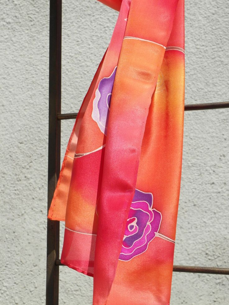 Red silk scarf, purple roses on orange and red background. I displayed it on iron rack outside of my workshop. Hand painted by SilkAgathe.