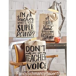 """Canvas Teacher Tote by Mud Pie Printed canvas tote bag. Choice of 3 different styles. """"I'M A teacher WHAT'S YOUR SUPER POWER,"""" """"DON'T make me use my TEACHER VOICE"""" and """"A TEACHER TAKES A Hand OPENS A"""