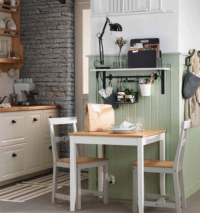 Mesita de madera cuadrada de base en blanco y cubierta de madera color natural con dos sillas que hacen juego también en madera en blanco y asiento de madera color natural. Este mini comedor se encuentra a un costado de la cocina, junto al muro enchapado de madera pintada verde claro.