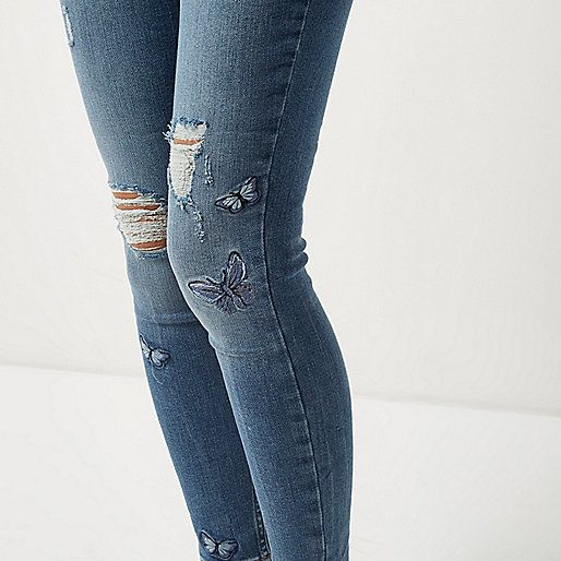 Mid blue wash denim Distressed detailing Embroidered butterfly detail  Mid rise Relaxed skinny fit Button and zip fly fastening