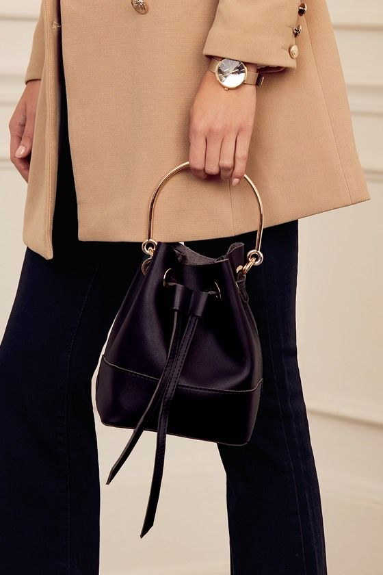 """Upgrade your staples with the Ellington Black Bucket Bag! Sleek vegan leather shapes this go-to bucket bag with a drawstring top (with gold grommets) and a roomy interior. Carry by the 52""""adjustable strap, or attach the matching gold hoop handle."""