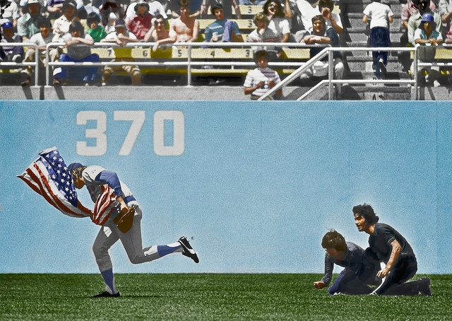 On April 25, 1976, Chicago Cubs outfielder Rick Monday saves the American flag from being burned in the Dodger Stadium outfield by two protesters.
