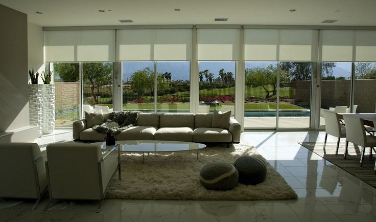 ... large main living areas where roller shades shield the late afternoon sun. Floor-to-ceiling Fleetwood glass sliders connect the interiors to the pool deck outside.