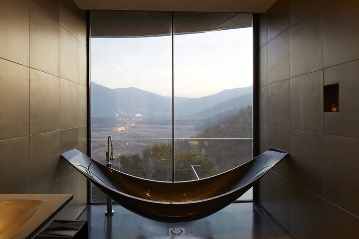 "At the Viña Vik, an ""avant-garde retreat and wine spa"" in Millahue, Chile, a carbon-fiber bathtub suspended from the ceiling is strategically positioned for Technicolor views of valleys and vineyards just outside the window. Designed by London's Splinter Works Studio, the VIK Master Suite's tub also boasts a foam-insulated core—meaning your hot baths stay steamy longer."