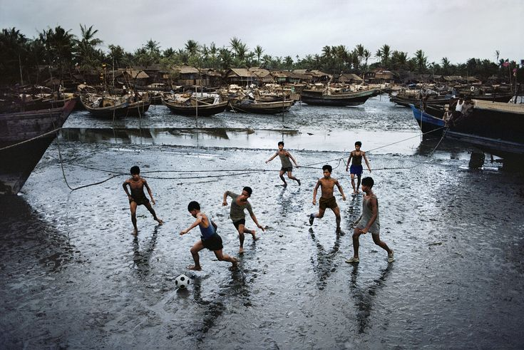 Sittwe, Burma. Even in the middle of the rainy season, these boys find space on the muddy bank of this river to play football. .