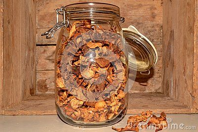 A glass Jar with dry chanterelle great taste mushroom yellow wooden background