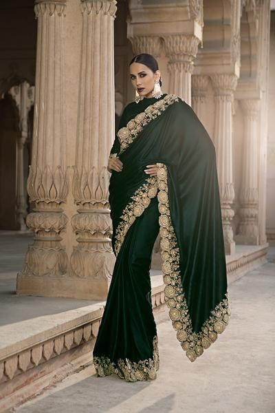 A bottle green velvet saree hand-crafted with golden dabka, beads and swarovski floral embroidery on border all-over. It is paired with a blouse piece of velvet fabric in bottle color with hand-embroidered border. This saree is appropriate for occasion such as parties, social gatherings, wedding party. By Meena Bazaar (MeenaBazaar.in)