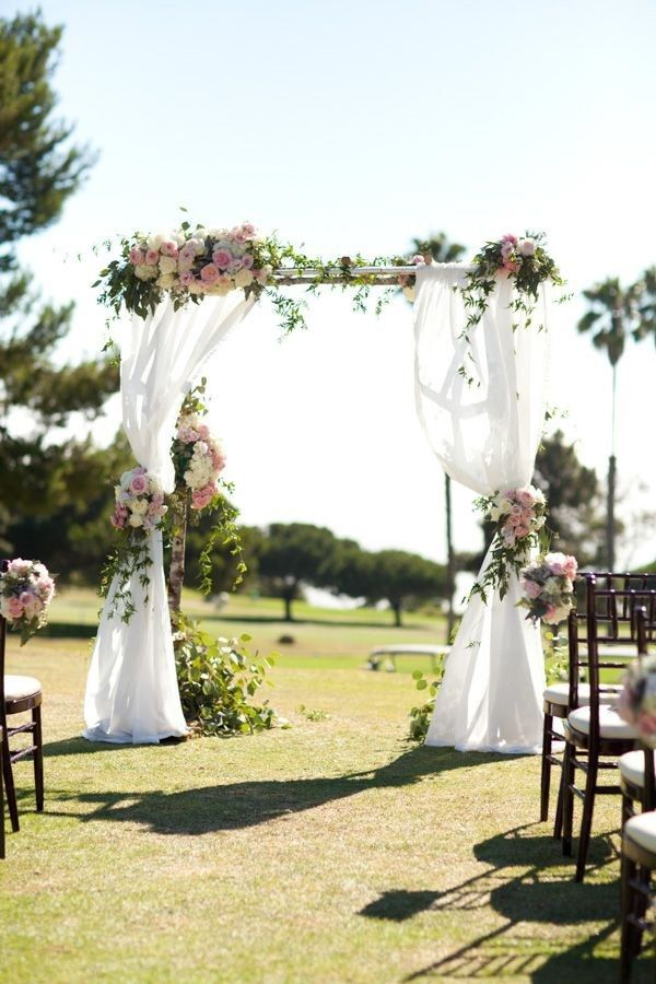 A sweet traditional floral wedding arch with dreamy organza curtains and blush pink flowers fit for an outdoor summer wedding.