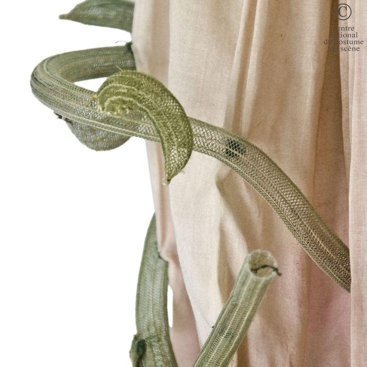 A flower 1977. DESIGNER: Emilio Carcano. COSTUME DESCRIPTION: Long dress in cotton dyed pink, trimmed with ornaments textile applications, painted hair green leaves and sisal. Gathers on the shoulder line and loose sleeves. Detail: